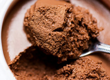 Chocolate Mousse In White Cup Bowl. Spoonful Visible  Spongy Texture With Pores. Vibrant Rich Brown Color. Macro Close Up