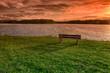 Bench on lake shore at sunset
