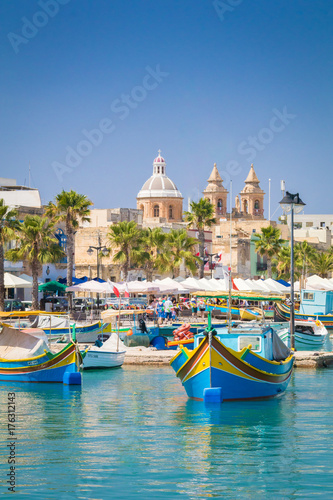Poster de jardin Europe Méditérranéenne Traditional colourful Maltese Luzzu fishing boats in the turquoise blue water of Marsaxlokk harbour, with the beautiful Parish Church of Our Lady of Pompei, Marsaxlokk, Malta, June 2017