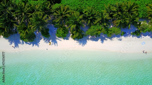 P01078 Aerial flying drone view of Maldives white sandy beach on sunny tropical paradise island with aqua blue sky sea water ocean 4k