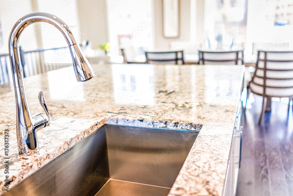 Fototapeta New modern faucet and kitchen room sink closeup with island and granite countertops in model house, home, apartment