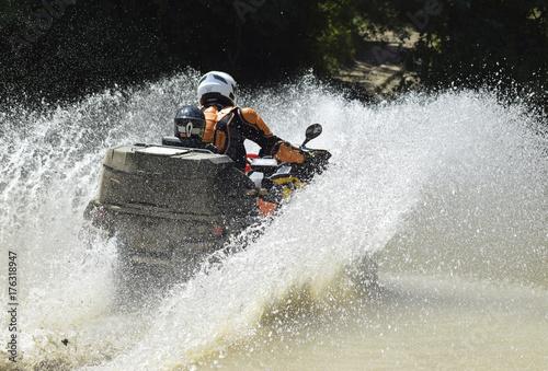 The man on the ATV crosses a stream