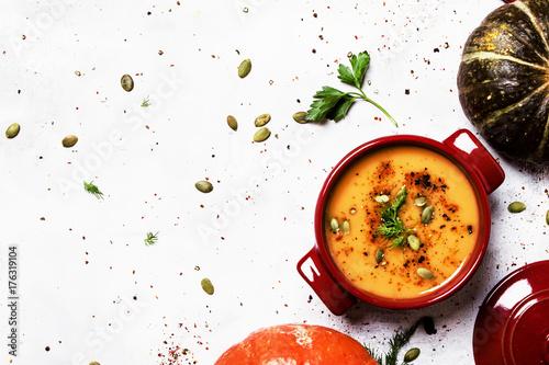 Fotografie, Obraz  Spicy pumpkin soup in a serving pan, top view