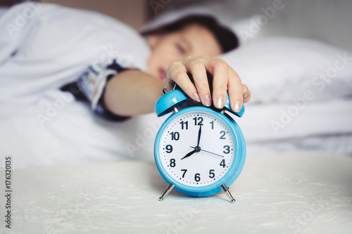 Wake up in the morning, Defocus Woman sleep on bedroom, Alarm  with time 8 o clock am, sleepy and lazy dont want getting out of bed Poster