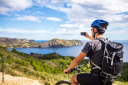 Canvastavla a young guy on a mountain bike trails in Spain and takes a photo on a white phone in the background of the Mediterranean sea of the rocky coast of the Costa Brava