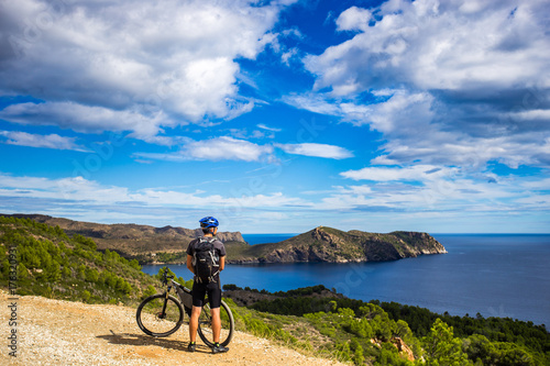 Photographie a young guy on a mountain bike trails in Spain and takes a photo on a white phone in the background of the Mediterranean sea of the rocky coast of the Costa Brava
