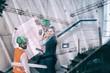 Composite image of colleagues looking plans against cranes