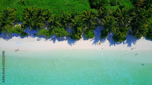 P01067 Aerial flying drone view of Maldives white sandy beach on sunny tropical paradise island with aqua blue sky sea water ocean 4k