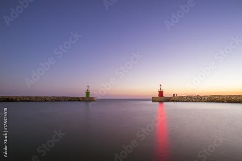 Zdjęcie XXL Seascape dwa mała latarnia morska z ich odbiciami na morzu przy zmierzchem. Niektórzy ludzie łowią pod rozgwieżdżonym niebem. Fotografia brać przy zmierzchem w Sabaudia plaży, Włochy