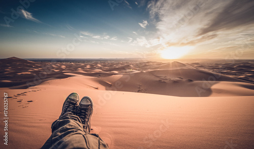 Poster Salmon A man is enjoying the sunset on the dunes in the Sahara Desert - Merzouga - Morocco