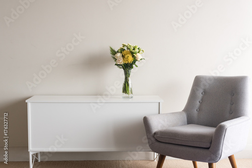 Fotografie, Tablou Grey retro armchair next to white sideboard with glass vase of cream and yellow
