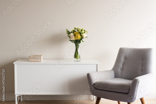 Valokuva Grey retro armchair next to white sideboard with rattan box and glass vase of cr
