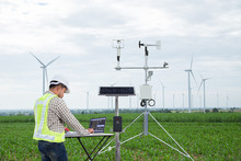 Engineer Using Computer Collect Data With Meteorological Instrument To Measure The Wind Speed, Temperature And Humidity And Solar Cell System On Corn Field Background, Agriculture Technology Concept
