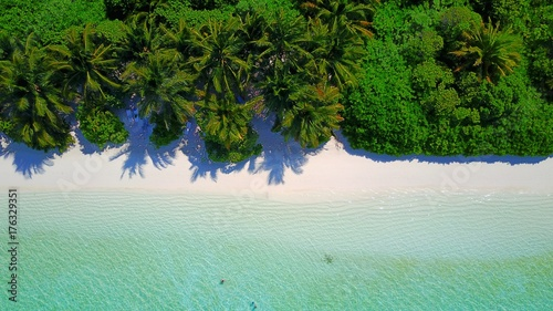 P01056 Aerial flying drone view of Maldives white sandy beach on sunny tropical paradise island with aqua blue sky sea water ocean 4k