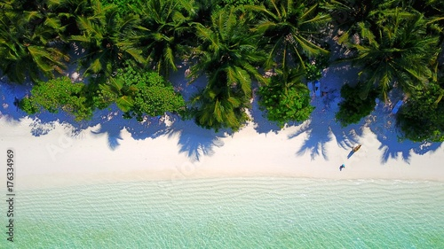 P01100 Aerial flying drone view of Maldives white sandy beach on sunny tropical paradise island with aqua blue sky sea water ocean 4k