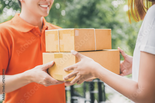 Smiling delivery man delivering parcel to a woman Wallpaper Mural