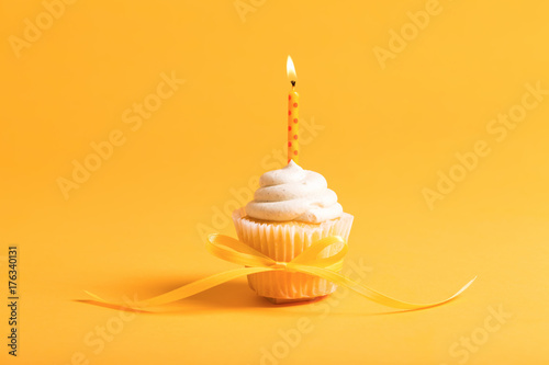Photo  Cupcake with candle celebration theme on a yellow background