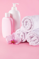 Obraz na płótnie Canvas Towels with shower gel and body lotion on pink background.