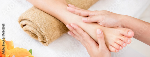 Therapist giving relaxing reflexology Thai foot massage treatment to a woman in spa