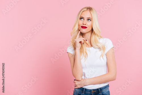 Picture of Pensive blonde woman looking up Fototapet