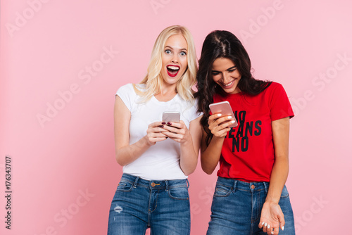 Fotografía  Laughing friends using smartphones and smiling isolated
