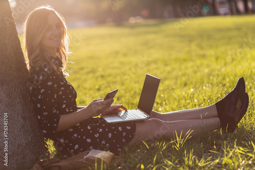 Portrait of beautiful young woman using technology while sitting outdoors