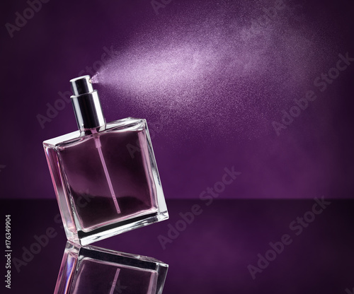 Fototapeta perfume bottle spraying on dark purple background obraz