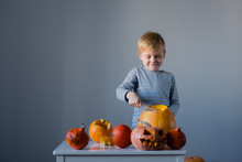 A Young Boy Carving A Pumpkin ...