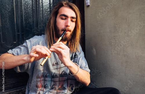 Plakat Młody człowiek wykonujący instrumentem flet na ulicy, młody człowiek wykonawca