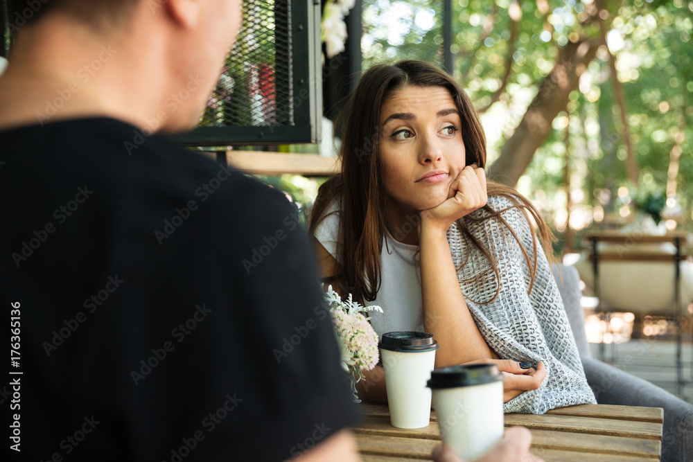Fototapety, obrazy: Tired bored girl sitting and drinking coffee