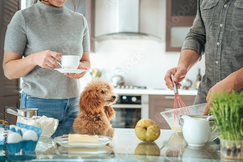 Poster Cuisine Couple with dog is making breakfast . Couple on the kitchen cooking together.