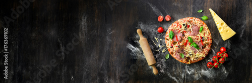 Girl hands making, decopating, preparing pizza with basil leaves on dark background. Top view, copy space. Banner