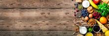 Healthy Breakfast Ingredients, Food Frame. Granola, Egg, Nuts, Fruits, Berries, Toast, Milk, Yogurt, Orange Juice, Cheese, Banana, Apple On Wooden Rustic Background, Top View, Copy Space. Banner