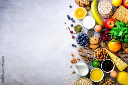 Obraz Healthy breakfast ingredients, food frame. Granola, egg, nuts, fruits, berries, toast, milk, yogurt, orange juice, cheese, banana, apple on light grey concrete background, top view, copy space. Banner - fototapety do salonu