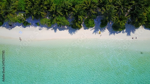 P01081 Aerial flying drone view of Maldives white sandy beach on sunny tropical paradise island with aqua blue sky sea water ocean 4k