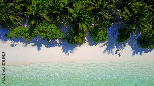 P01109 Aerial flying drone view of Maldives white sandy beach on sunny tropical paradise island with aqua blue sky sea water ocean 4k