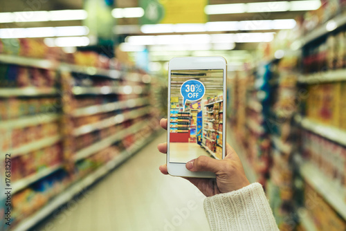 Photo Woman doing grocery shopping at supermarket and viewing offers with help of augm