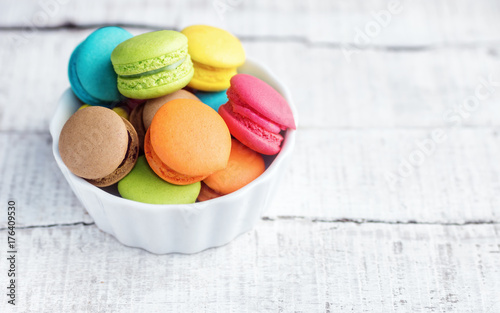 Poster Macarons Vibrant colorfull macarons in plate on white wooden table. Text space