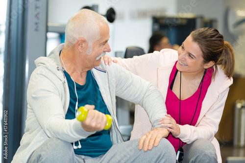 Plakat starszy człowiek i jego trener uśmiechnięty