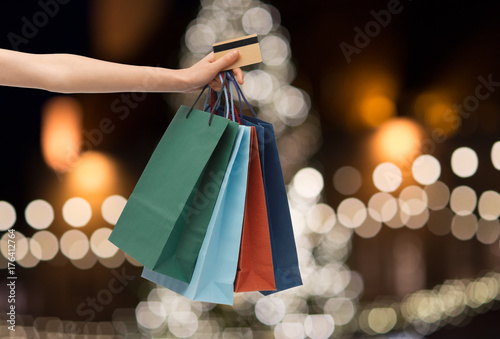 Fototapeta shopping bags and credit card in hand at christmas obraz
