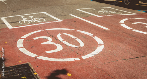 Keuken foto achterwand Route 66 white paint on a red road indicating presence of a bicycle and forbidden to exceed the speed of 30