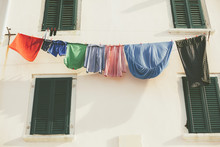 Clothes Hanging On A Line On A Shuttered Building