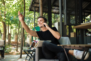 Portrait of a happy cheerful man talking on mobile phone