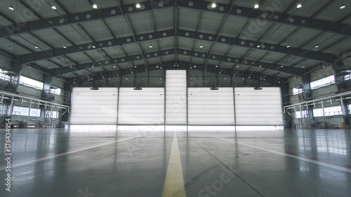 Fototapeta Roller shutter door and concrete floor inside factory building for industrial background. Airplane in front of half opened door to hangar. The open door of the hangar. Mechanic opening the door obraz