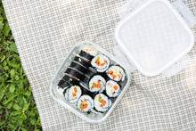 Sushi In Glass Container On Picnic Cloth On Green Grass With Shadow Of Sunlight