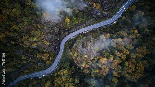 Montage in der Fensternische Luftaufnahme street from above trough a misty forest at autumn, aerial view flying through the clouds with fog and trees