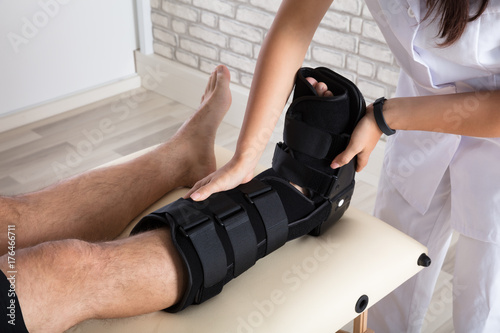 Cuadros en Lienzo Orthopedist Putting Walking Brace To Patient's Leg