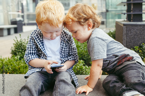 Two cute adorable white Caucasian toddlers boys sitting together and playing games on cell mobile phone digital tablet. Candid lifestyle and early development concept. New technology generation.