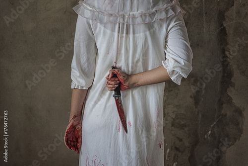 Woman holding knife back on her hand with blood Canvas Print