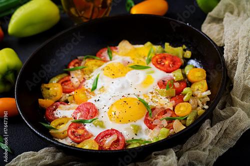 Deurstickers Gebakken Eieren Fried eggs with vegetables - shakshuka in a frying pan on a black background